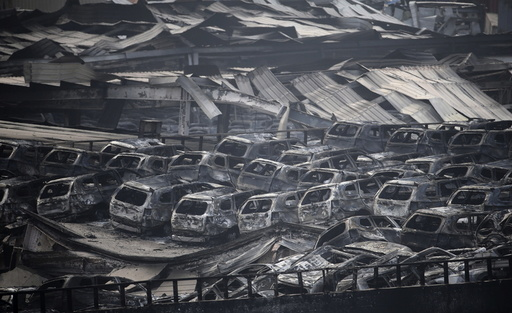 Damaged vehicles are seen at the site of explosions in Tianjin