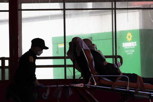 Emergency medical technicians transport a patient to Elmhurst Hospital Center emergency room, Saturday, April 4, 2020 in the Queens borough of New York. The new coronavirus causes mild or moderate symptoms for most people, but for some, especially older adults and people with existing health problems, it can cause more severe illness or death. (AP Photo/Mary Altaffer)