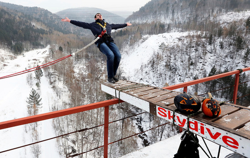 Member of Exit Point amateur rope-jumping group jumps from water pipe bridge to mark end of group's jumping season and recent Halloween festivities outside Krasnoyarsk