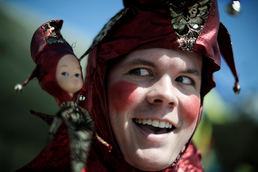 Jamie Oberg clowns for the camera as a court jester at the St Ives Medieval Fair in Sydney, one of the largest of its kind in Australia