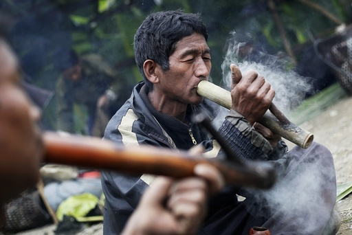Men smoke opium from traditional pipes made out of bamboo at a hunting base camp in an opium field during a hunting trip between Donhe and Lahe township in the Naga Self-Administered Zone