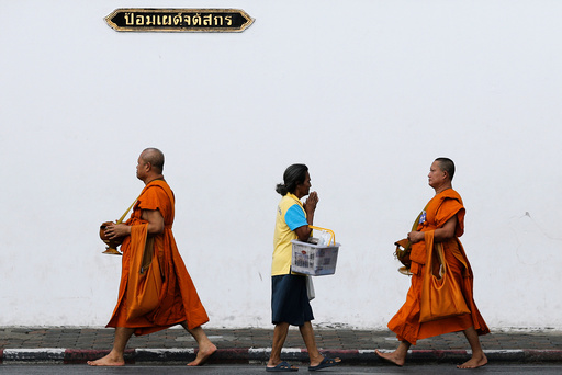 A woman greets Buddhist monks as they arrive for a ceremony at the Grand Palace to commemorate Thailand's King Bhumibol Adulyadej's 70th anniversary on the throne
