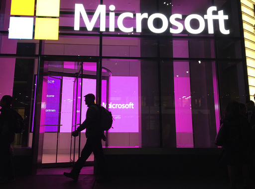 FILE - In this Nov. 10, 2016, file photo, people walk past a Microsoft office in New York.  Microsoft says, Wednesday, Aug. 4, 2021,  employees must be fully vaccinated to enter the company's U.S. offices and other worksites, starting next month. The tech giant told employees it will require proof of vaccination for all employees, vendors, and any guests entering Microsoft buildings in the U.S.(AP Photo/Swayne B. Hall, File)
