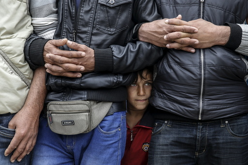 Migrants and refugees gather to listen to Taha, an Iraqi woman of the Yazidi faith who was abducted and held by the Islamic State for three months, at the Greek-Macedonian border near the village of Idomeni