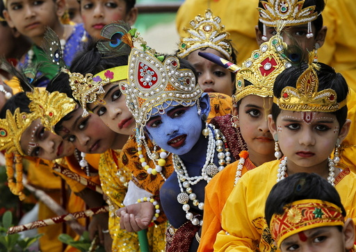 Schoolchildren dressed as Hindu Lord Krishna wait to perform during celebrations on the eve of the Janmashtami festival in Chandigarh