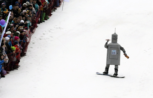 Spectators watch a snowboarder in a fancy costume, slides down before an attempt to cross a pool of water at the foot of a ski slope at the Bobrovy Log ski resort on the suburbs of the Siberian city of Krasnoyarsk