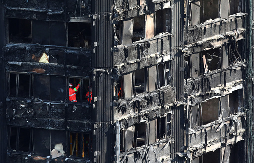 Members of the emergency services work inside burnt out remains of the Grenfell apartment tower in North Kensington, London