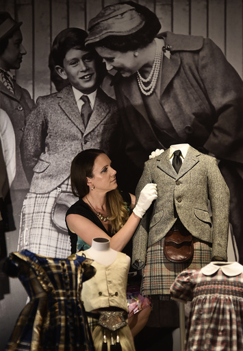 Curator of Royal Collection Trust Anna Reynolds poses with a kilt and jacket belonging to Prince Charles from 1958 at Buckingham Palace in central London