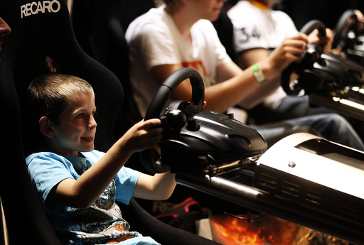Visitors play ''Gran Turismo'' at an exhibition stand at the Gamescom 2010 fair in Cologne