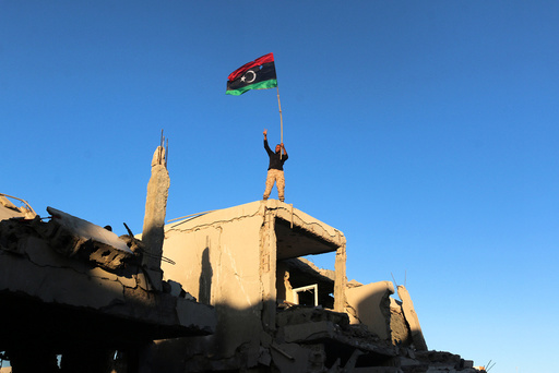 Fighter of Libyan forces waving a Libyan flag flashes victory sign as he stands atop the ruins of a house after forces finished clearing Ghiza Bahriya, the final district of the former Islamic State stronghold of Sirte