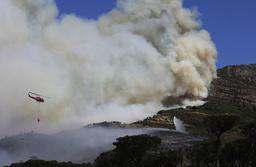 Helikoptre slipper vann ved Rhodes Memorial på Table Mountain i Cape Town. Foto: Nardus Engelbrecht / AP / NTB
