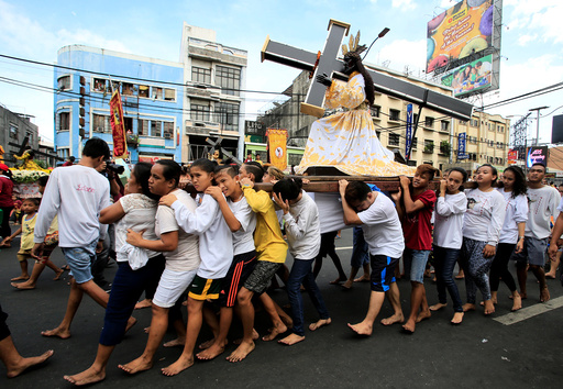Barefoot devotees parade with replica of a Black Nazarene two days before the annual procession of the Black Nazarene in metro Manila