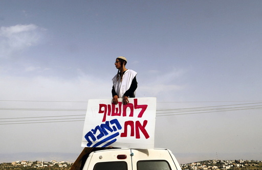 An Israeli right-wing activist takes part in a protest calling for the release of suspected Jewish attackers outside the West Bank village of Duma near Nablus