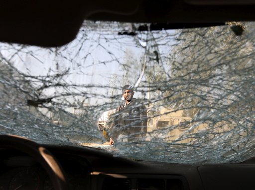 An Afghan man is seen through the cracked side window of a vehicle at the site of a suicide car bomb attack in Surkhrod district of Nangarhar province