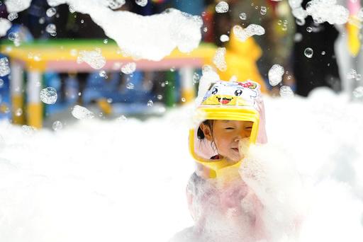 Child plays inside a pool filed with foam bubbles in Huaian, Jiangsu