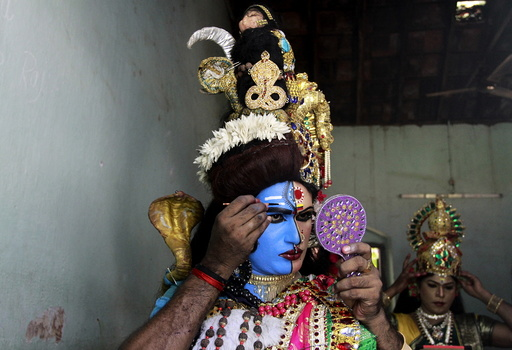 A man dressed as Hindu God Ardhnarishwar gets ready to take part in a performance during festivities marking the start of the annual harvest festival of