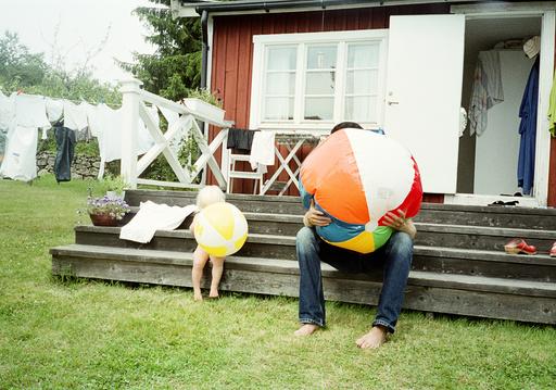 Fahter and daughter inflating beach balls, Blekinge, Sweden.