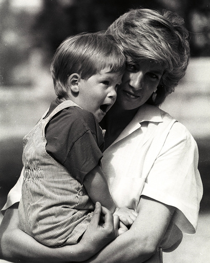 Prince Harry yawns as his mother Princess Diana holds him during a morning picture session at Marivet Palace