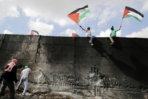 Palestinian protester tries to hammer a hole through the Israeli barrier that separates the West Bank town of Abu Dis from Jerusalem, as others wave Palestinian flags during clashes with Israeli troops