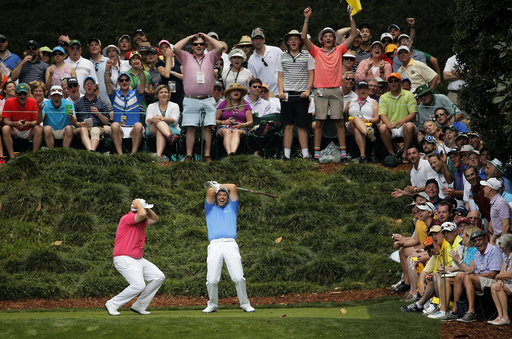 Harrington of Ireland reacts after missing a hole-in-one on the 9th tee with fellow countryman Lowry during the par 3 event held ahead of the 2015 Masters at Augusta National Golf Course in Augusta