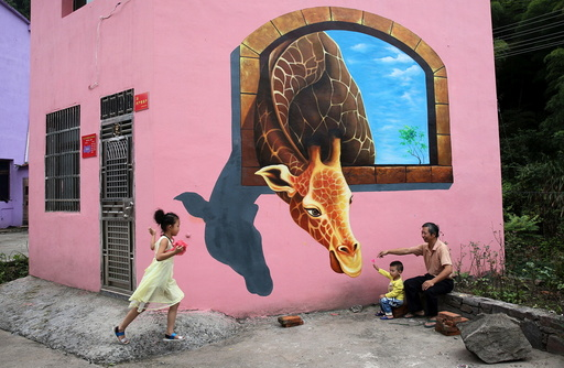 Tourists play in front of3D painting on wall of house in Luoyuan village, Jinhua