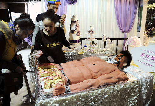 A staff member looks on next to a cake, which was baked in the shape of a muscular man, for customers to try for free during a promotional event of a cake store in Shenyang