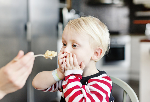 Boy covering mouth while hand feeding him at home