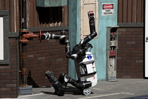 The Jet Propulsion Lab team's RoboSimian robot turns a valve on a simulated disaster-response course during day one of the DARPA Robotics Challenge finals in Pomona