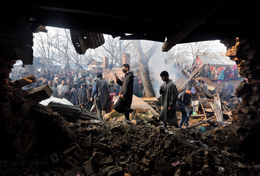 People walk on the rubble of a house which according to the local media was damaged in a gunbattle between suspected militants and Indian security forces in Batmurran village