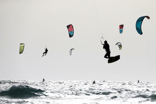 People kitesurf in the Mediterranean sea in Tel Aviv