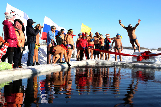 A winter swimmer jumps into icy water to celebrate with other members the establishment of a winter swimming club in Heihe