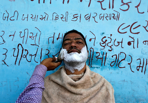 A man gets a shave from a roadside barber in Ahmedabad