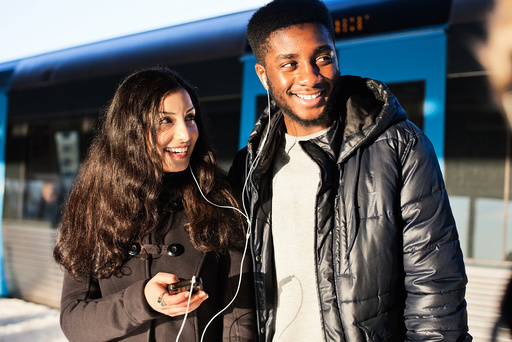 Happy young friends listening music through hands-free device against train