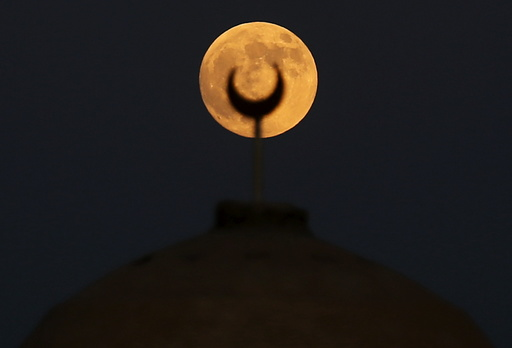 A supermoon, the last of this year's supermoons, rises over a minaret of a mosque in Wadi El-Rayan Lake at the desert of Al Fayoum Governorate, south west of Cairo