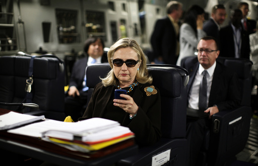 U.S. Secretary of State Hillary Clinton checks her PDA upon her departure in a military C-17 plane from Malta bound for Tripoli, Libya