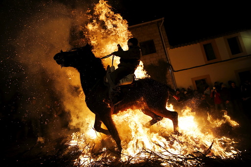 A man rides a horse through the flames during the