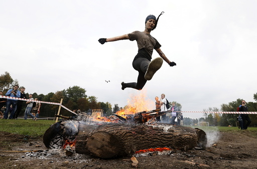 Woman jumps over the fire as she takes part in an extreme run competition in Zhodino
