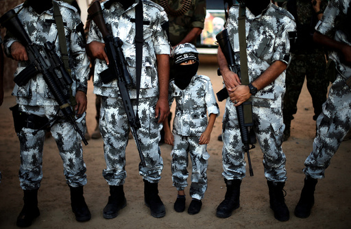 A Palestinian boy stands between militants of the Popular Resistance Committees during a military parade in Rafah