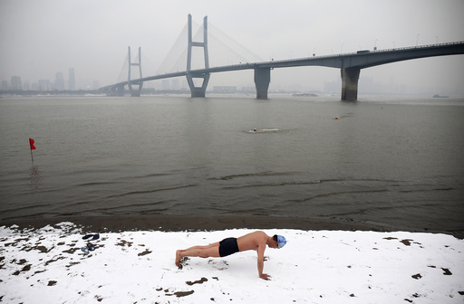 A winter swimmer does push-ups on the snow-covered banks of the Yangtze River, in Wuhan