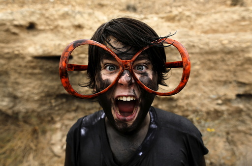 Jose, a reveller covered in grease, poses for a photo as he takes part in the annual Cascamorras festival in Baza, southern Spain
