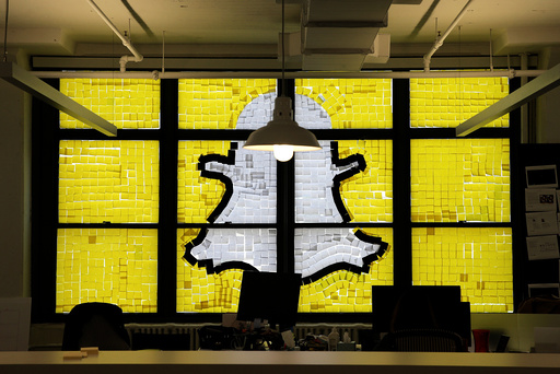 Snapchat logo image created with Post-it notes is seen in the windows of Havas Worldwide offices at 200 Hudson street in lower Manhattan, New York during Post-it note war