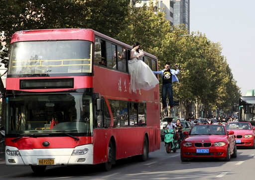 Magician Lei is seen suspended outside a double-deck bus, next to a woman in a wedding gown, as they participate in a performance on a street in Zhengzhou