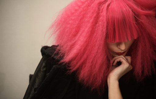 A model wearing a wig waits backstage for the start of the Agatha Ruiz de la Prada's Fall/Winter 2014 collection during the Mercedes-Benz Fashion Week in Madrid