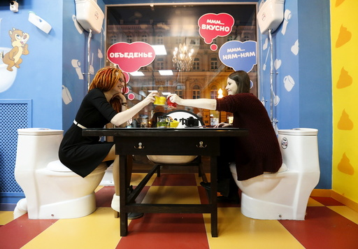 Customers clink cups as they sit at Crazy Toilet Cafe in central Moscow