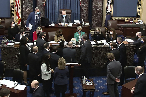 In this image from video, senators, staff and attorney's gather after Sen. Mike Lee, R-Utah, made a point of order as House impeachment manager Rep. Madeleine Dean, D-Pa., spoke during closing arguments in the second impeachment trial of former President Donald Trump in the Senate at the U.S. Capitol in Washington, Saturday, Feb. 13, 2021. (Senate Television via AP)