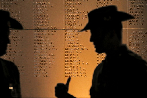 Two Australian soldiers cast shadows on a monument for soldiers during the dawn service to mark the ANZAC commemoration ceremony at the Australian National Memorial in Villers-Bretonneux