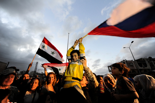 People celebrate carrying a Russian and Syrian national flags inside Waer district, after rebel fighters and their families evacuated the besieged Waer district in the central Syrian city of Homs