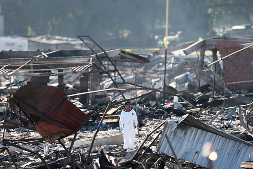 An investigator stands amidst the wreckage of houses destroyed in an explosion at the San Pablito fireworks market in Tultepec
