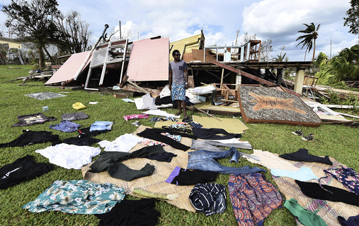 Local resident stands near clothes laid out to dry near damaged home in Port Vila