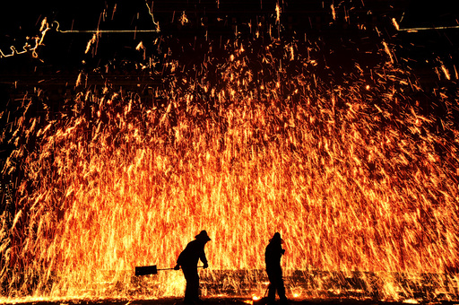 Local artists perform folk art of making shower of sparks from molten iron during an event celebrating China's Lunar New Year in Anyang